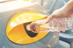 Mano dell'uomo del primo piano che getta bottiglia di acqua di plastica vuota nei rifiuti Ricicli lo scomparto fotografia stock libera da diritti