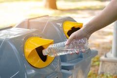 Mano dell'uomo del primo piano che getta bottiglia di acqua di plastica vuota nei rifiuti Ricicli lo scomparto immagini stock