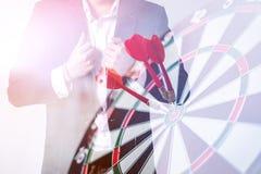 Mano dell'uomo di affari con i dardi che colpiscono il centro Fotografie Stock