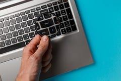 Mano dell'uomo e del computer portatile con la lente d'ingrandimento immagini stock