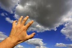 Mano dell'uomo sul fondo del cielo Fotografia Stock Libera da Diritti