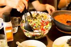 Mano della cena della famiglia che tiene grande cucchiaio con l'insalata della verdura fresca Fotografia Stock Libera da Diritti