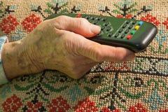 Mano della donna anziana con il driver della TV Immagini Stock