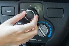 Mano della donna che accende il sistema di condizionamento d'aria dell'automobile Fotografia Stock Libera da Diritti