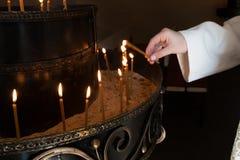 Mano della donna che accende le candele Immagine Stock