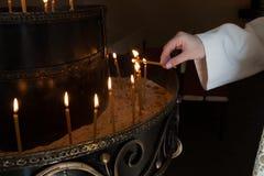 Mano della donna che accende le candele Fotografia Stock Libera da Diritti