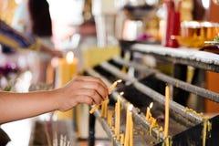 Mano della donna che accende le candele in una chiesa Fotografie Stock Libere da Diritti