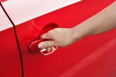 Mano della donna che apre la porta di automobile rossa, primo piano Fotografia Stock