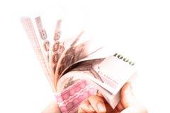 Mano della donna che conta un pacchetto della banconota di baht tailandese 1.000 Immagine Stock