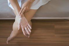 Mano della donna che controlla il suo impulso con due dita sul polso a casa fotografia stock