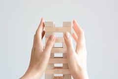 Mano della donna che costruisce una torre con blocchi di legno su un fondo bianco Fotografia Stock