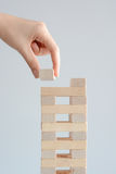 Mano della donna che costruisce una torre con blocchi di legno su un fondo bianco Fotografia Stock Libera da Diritti