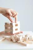 Mano della donna che costruisce una torre con blocchi di legno su un fondo bianco Immagine Stock Libera da Diritti