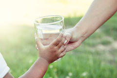 Mano della donna che dà vetro di acqua dolce al bambino nel parco Fotografia Stock