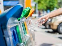 Mano della donna che getta bottiglia di acqua di plastica vuota nel recipiente di riciclaggio Fotografie Stock