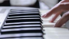 Mano della donna che gioca una fine del sintetizzatore della tastiera del regolatore del MIDI su archivi video