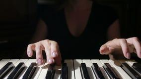 Mano della donna che gioca una fine del sintetizzatore della tastiera del regolatore del MIDI su stock footage