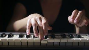 Mano della donna che gioca una fine del sintetizzatore della tastiera del regolatore del MIDI su video d archivio