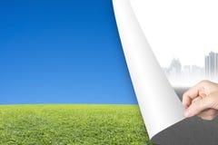 Mano della donna che gira l'erba rivelante del cielo della pagina grigia di paesaggio urbano Immagini Stock