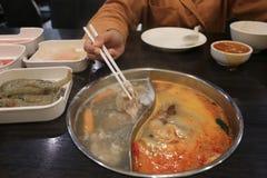 Mano della donna che giudica i bastoncini di carne di maiale affettata fresca crudi con le verdure per lo shabu di shabu o di cot fotografia stock