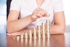 Mano della donna che impila la moneta di oro Immagini Stock