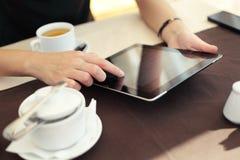 Mano della donna che indica allo schermo attivabile al tatto della compressa in caffè Fotografia Stock Libera da Diritti