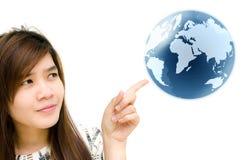 Mano della donna che indica il globo della terra. Fotografia Stock