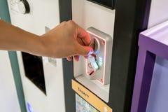 Mano della donna che inserisce le monete nel distributore automatico fotografia stock libera da diritti