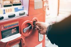 Mano della donna che inserisce moneta nel distributore automatico al pubblico della via fotografie stock