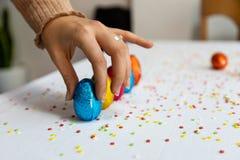 Mano della donna che installa le uova di Pasqua variopinte del cioccolato fotografia stock libera da diritti