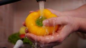 Mano della donna che lava peperone dolce giallo al lavandino di cucina stock footage