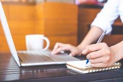Mano della donna che lavora ad un computer portatile e che scrive con una penna Immagine Stock