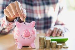 Mano della donna che mette moneta nel porcellino salvadanaio Ricchezza di risparmio dei soldi e immagine stock