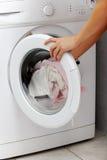 Mano della donna che mette un panno nella lavatrice   fotografia stock