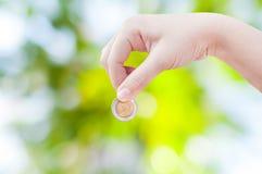 Mano della donna che mette una moneta sul fondo verde della natura, risparmiante Fotografie Stock