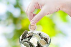 Mano della donna che mette una moneta sul fondo verde della natura, risparmiante Fotografie Stock Libere da Diritti