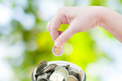 Mano della donna che mette una moneta sul fondo verde della natura, risparmiante Immagini Stock