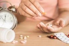 Mano della donna che prende le pillole con bicchiere d'acqua e l'orologio sullo scrittorio, fotografie stock