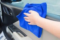 Mano della donna che pulisce il pannello interno della porta di automobile con il grumo del microfiber Fotografie Stock Libere da Diritti