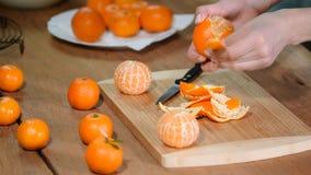Mano della donna che sbuccia mandarino dolce maturo, fine su stock footage