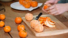 Mano della donna che sbuccia mandarino dolce maturo, fine su archivi video