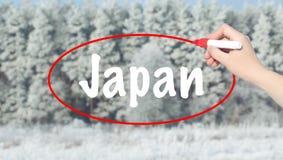 Mano della donna che scrive il Giappone con un indicatore sopra la foresta di inverno Fotografia Stock