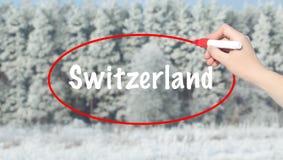 Mano della donna che scrive la Svizzera con un indicatore sopra la foresta di inverno Fotografia Stock Libera da Diritti