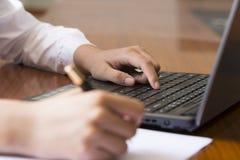 Mano della donna che scrive un contratto con un computer portatile accanto Fotografia Stock