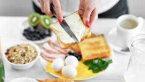 Mano della donna che spande burro cremoso su pane tostato appetitoso fresco facendo uso del primo piano del coltello video d archivio