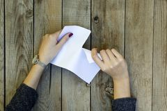 Mano della donna che strappa il Libro Bianco immagini stock libere da diritti