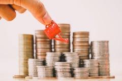 Mano della donna che tiene annaffiatoio rosso sulla pila dei soldi fotografia stock libera da diritti