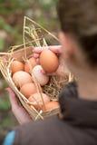 Mano della donna che tiene canestro di vimini con le uova fresche su erba verde Fotografie Stock Libere da Diritti
