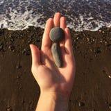 Mano della donna che tiene il mare blu vicino disponibile delle piccole pietre su un fondo della spiaggia fotografia stock libera da diritti
