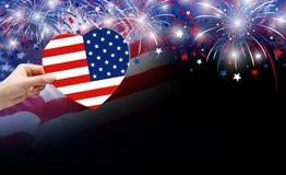 Mano della donna che tiene la bandiera di U.S.A. in cuore e fuochi d'artificio di forma Immagini Stock Libere da Diritti